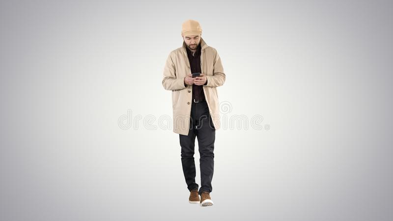 Handsome man in cloak walking and texting message on the phone on gradient background. stock photography