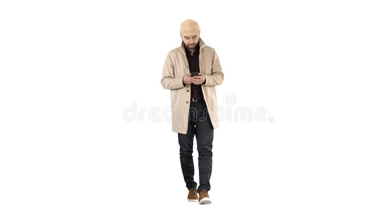 Handsome man in cloak walking and texting message on the phone on white background. royalty free stock images