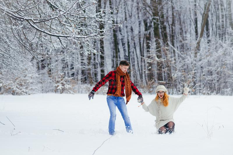 Full-length shot of the happy loving couple holding hands and running along the snowy forest. The beautiful red head royalty free stock photography