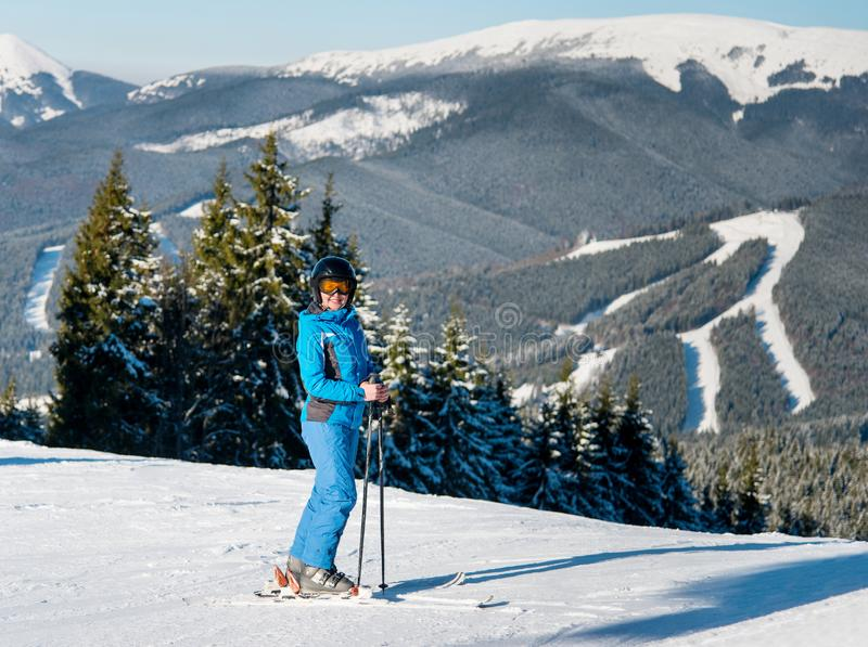 Full length shot of a happy woman skier skiing on the slope at winter ski resort in sunny beautiful day stock photo