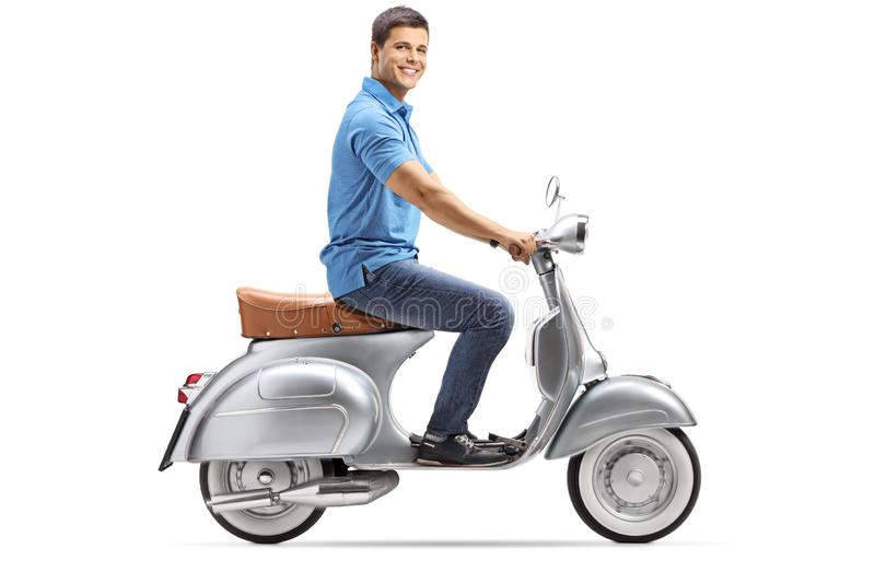 Full length shot of a happy young man riding a vintage scooter and looking at the camera. Isolated on white background royalty free stock images