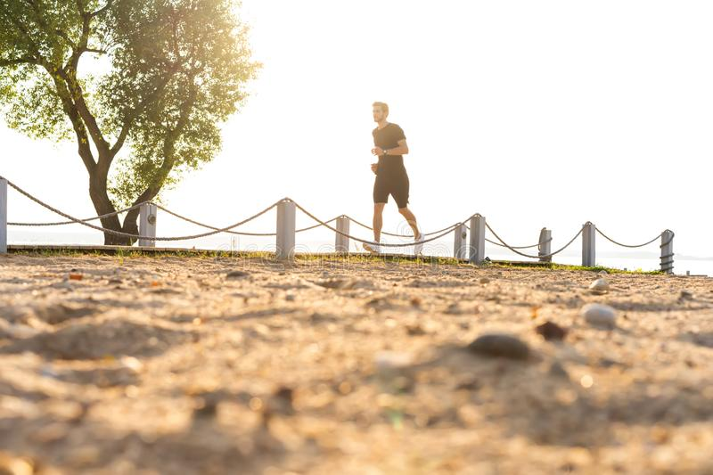 Full length shot of healthy young man running on the promenade. Male runner sprinting outdoors stock photography