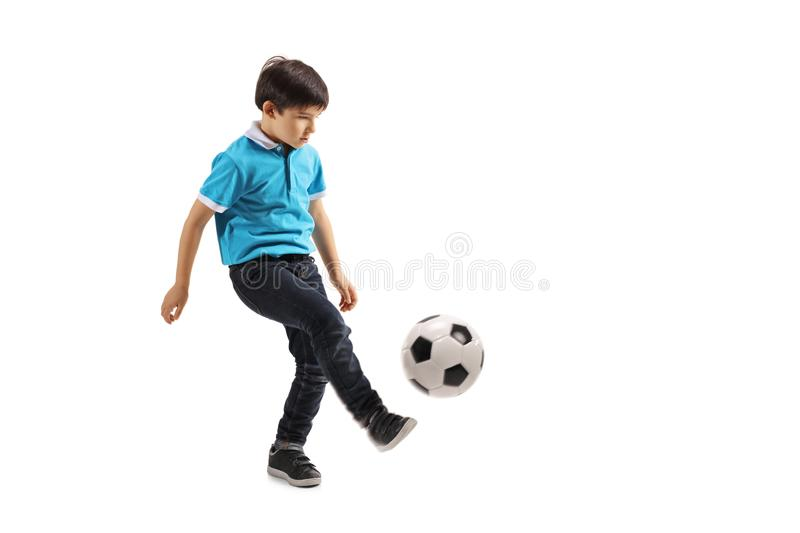 Full length shot of a little boy playing soccer. Isolated on white background stock photo