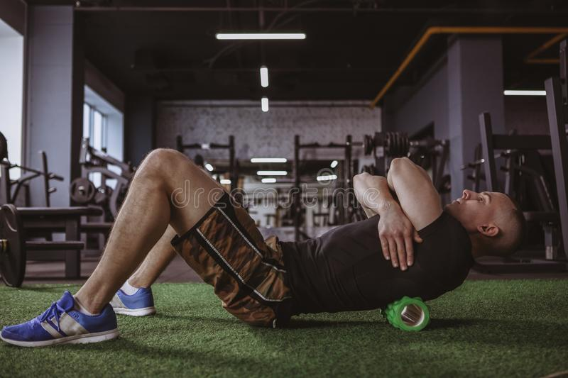 Male athlete using foam roller at the gym royalty free stock photo