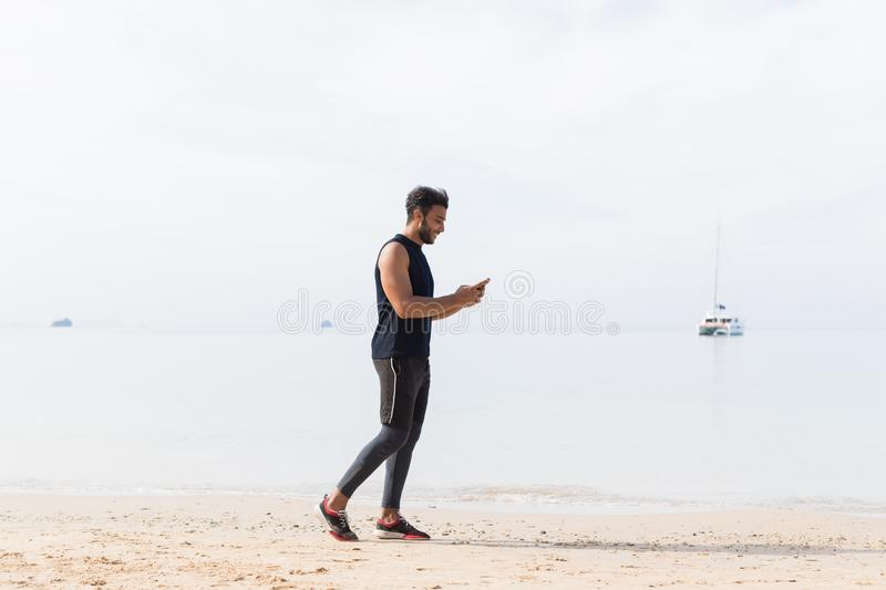 Full Length Shot Of Male Runner Using Cell Smart Phone On Beach While Jogging On Seaside Man Young Latin Sport. Healthy Lifestyle Concept stock photo