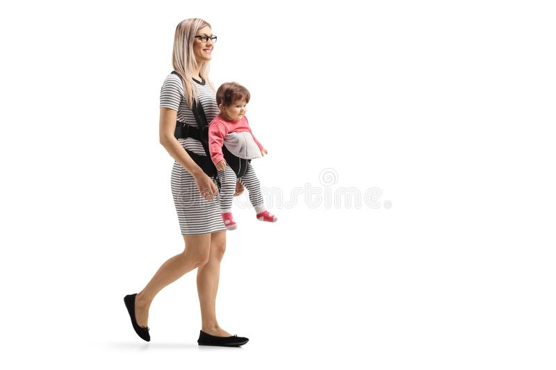 Mother walking with a baby in a carrier. Full length shot of a mother walking with a baby in a carrier isolated on white background stock photos