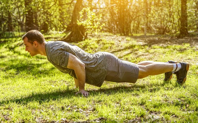 Full length shot of muscular man does push-ups from green grass in park. Full length shot of muscular man does push-ups from field ground covered green grass in stock images