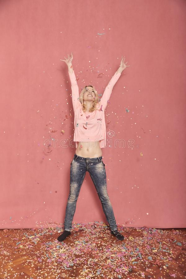 Full length shot, one young happy, smiling woman arms outstretched high in air with confetti falling down on floor. 20-29 years old, long blond hair. Shot in stock photos