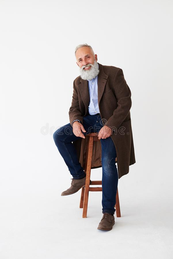 Positive mature bearded man in coat sitting on chair in studio royalty free stock photos