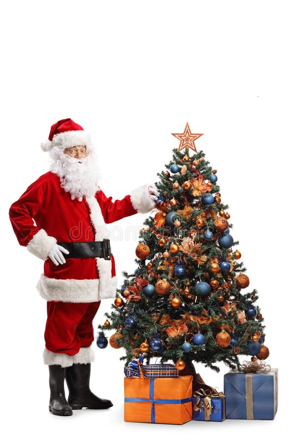 Full length shot of Santa Claus decorating a Christmas tree and looking at the camer. A isolated on white background royalty free stock images