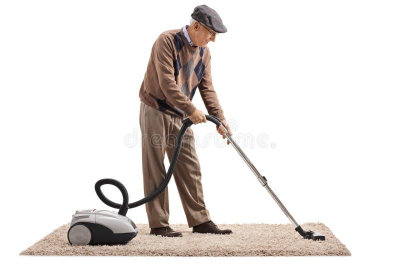 Senior man vacuuming a carpet. Full length shot of a senior man vacuuming a carpet isolated on white background stock photo