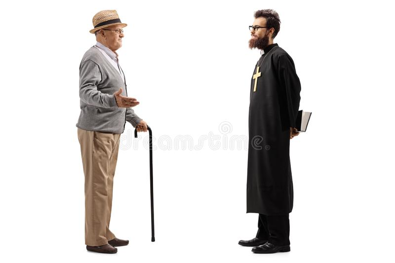 Full length shot of a senior man with cane talking to a priest royalty free stock photography