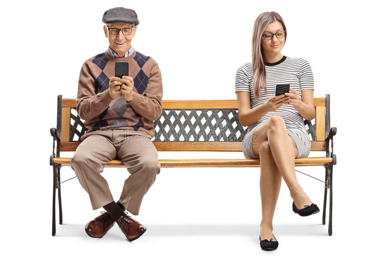 Senior man and a young lady sitting on a bench with smartphones royalty free stock image