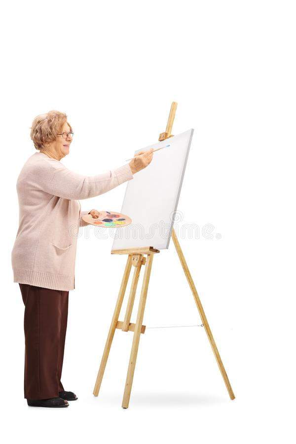 Senior woman painting on a canvas. Full length shot of a senior woman painting on a canvas isolated on white background stock photos