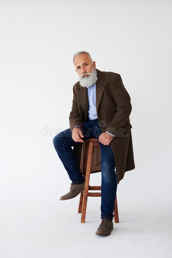 Serious mature bearded man in coat sitting on chair in studio stock photo