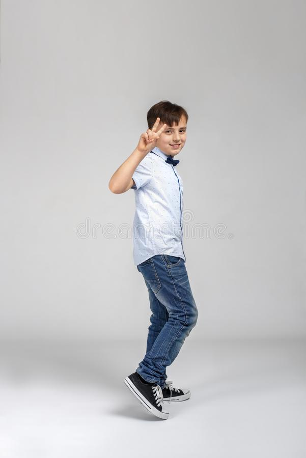 Studio shot of a smiling boy wearing a blue shirt and jeans walking and showing a gesture of victory on grey background. Full length shot of a smiling boy stock images