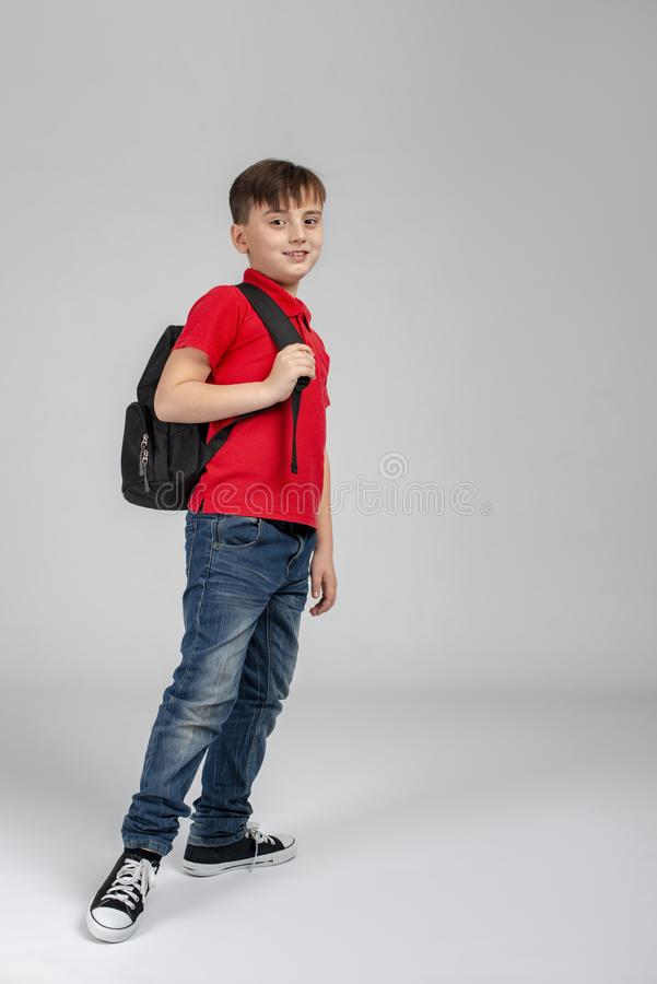Studio shot of a smiling boy wearing a red shirt and jeans walking with backpack on grey background in studio. Full length shot of a smiling boy wearing a red royalty free stock image