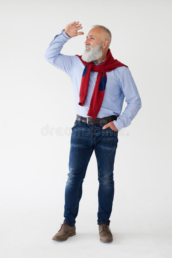Smiling senior bearded man looking sideway, holding hands near f royalty free stock photos