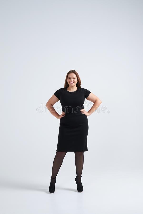 Smiling woman in black dress holding hands on waist. Full-length shot of smiling woman in black dress holding hands on waist stock photos