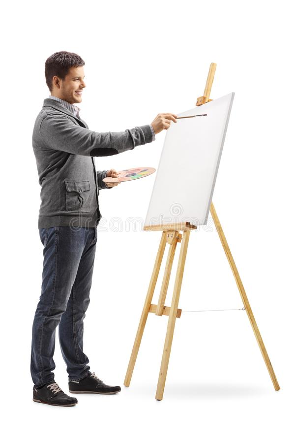 Smiling young man painting on a canvas. Full length shot of a smiling young man painting on a canvas isolated on white background stock photos