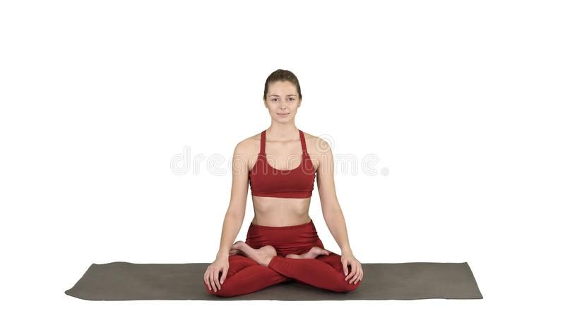 Sporty attractive woman practicing yoga, sitting in Lotus exercise, Siddhasana pose breathing on white background. stock image