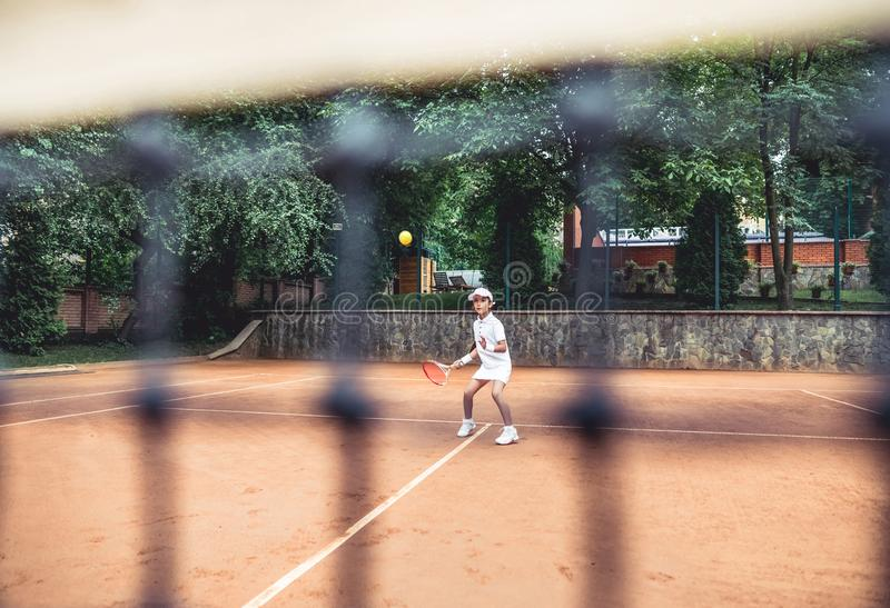 Full length shot of a sporty little girl on open tennis court. Child girl athlete playing tennis in the sport club. Active. Exercise for kids, action, activity stock image