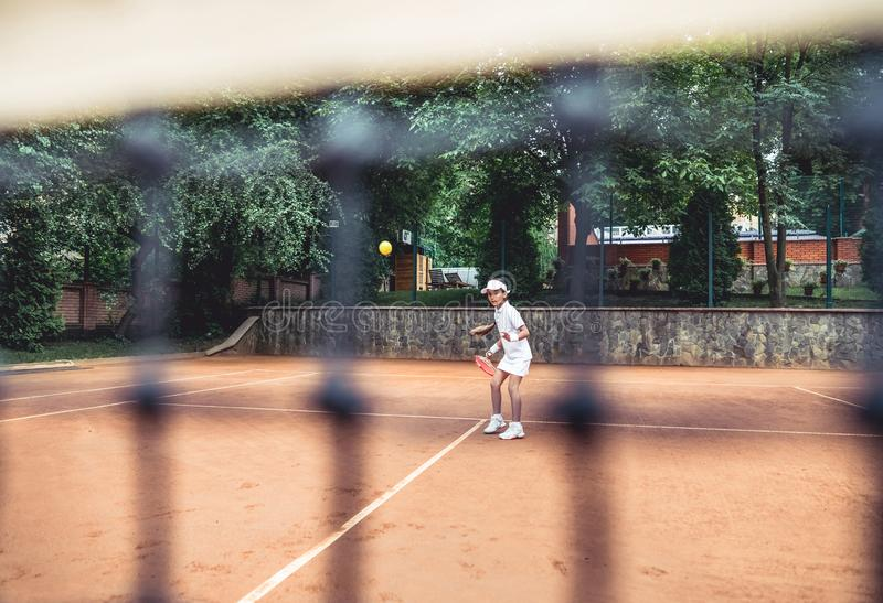 Full length shot of a sporty little girl on open tennis court. Child girl athlete playing tennis in the sport club. Active. Exercise for kids, action, activity royalty free stock photo