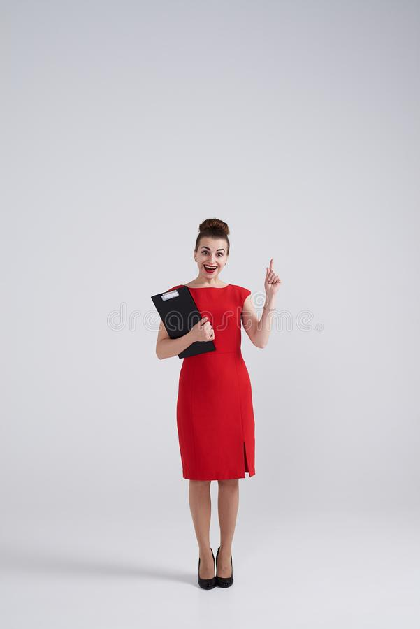 Surprised businesswoman holding folder and pointing upward. Full-length shot of surprised businesswoman holding folder and pointing upward royalty free stock photos