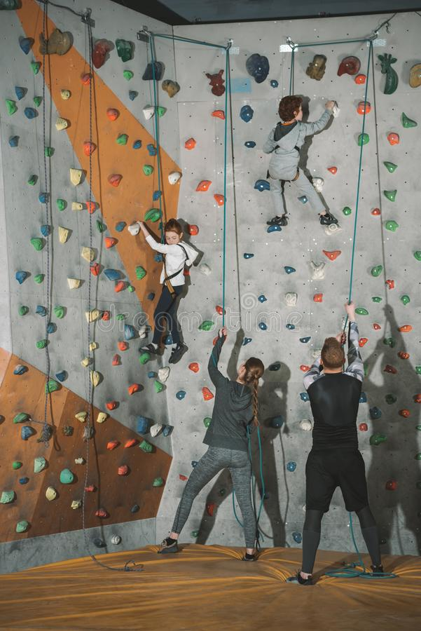 Full-length shot of two little kids climbing a wall at gym and their mother and father holding. Securing ropes stock image