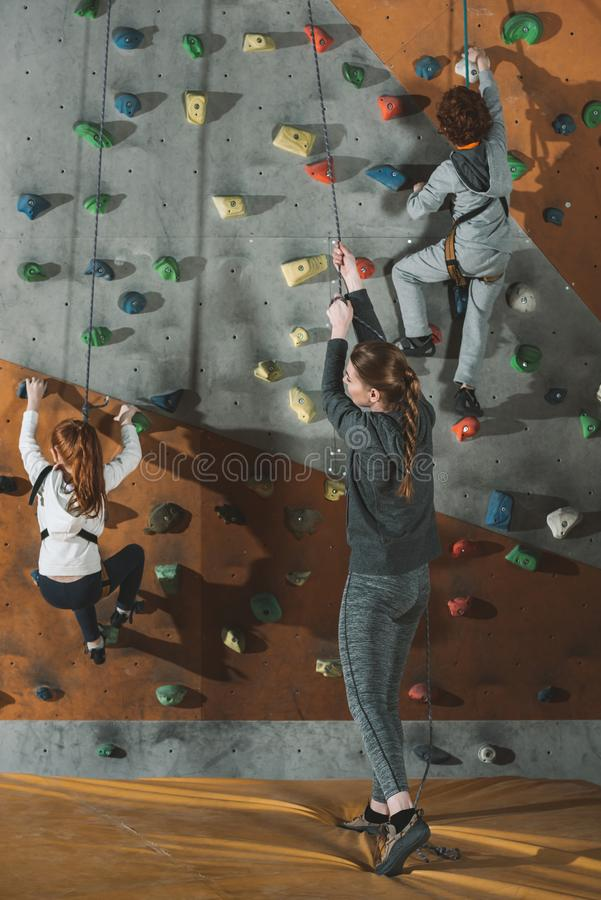 Full-length shot of two little kids climbing a wall at gym and their mother holding. Securing rope royalty free stock photo