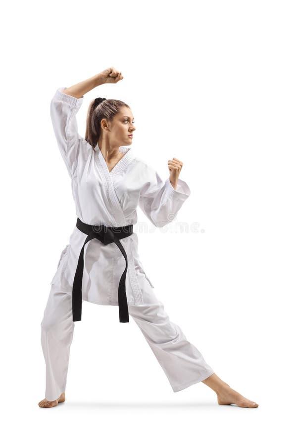Woman with black belt and kimono practicing karate kata stock photography