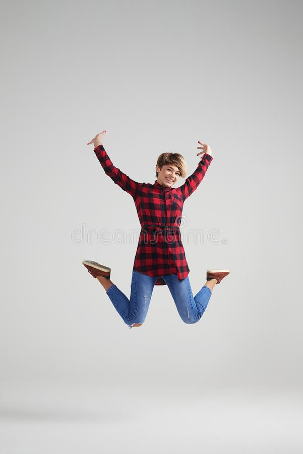 Woman with stylish haircut jumping at studio royalty free stock image