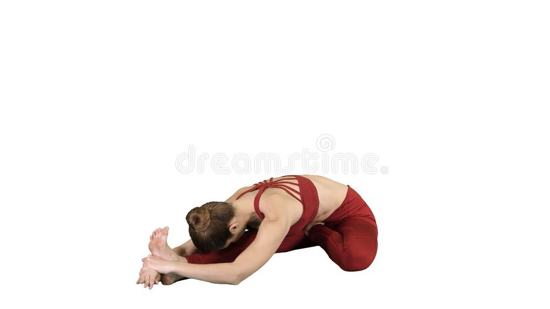 Young attractive woman practicing yoga, sitting in Head to Knee Forward Bend exercise, Janu Sirsasana pose on white stock images