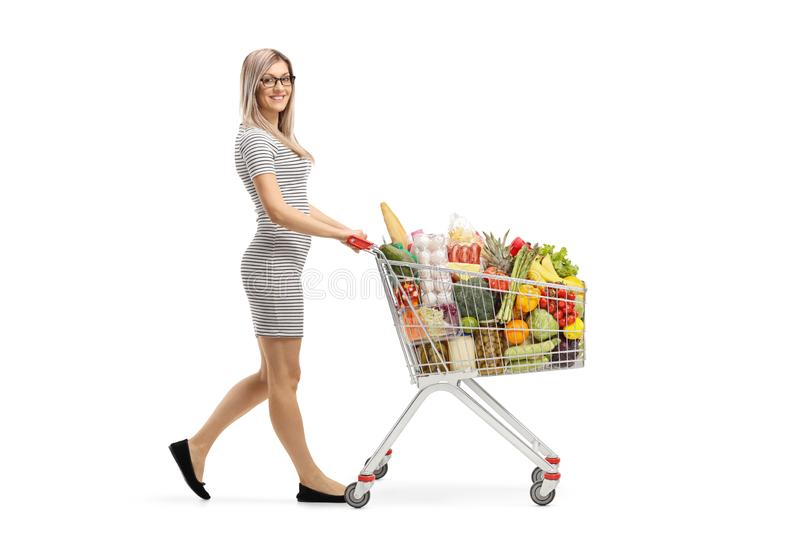 Full length shot of a young attractive woman pushing a shopping cart with food products and smiling at the camera. Isolated on white background royalty free stock image
