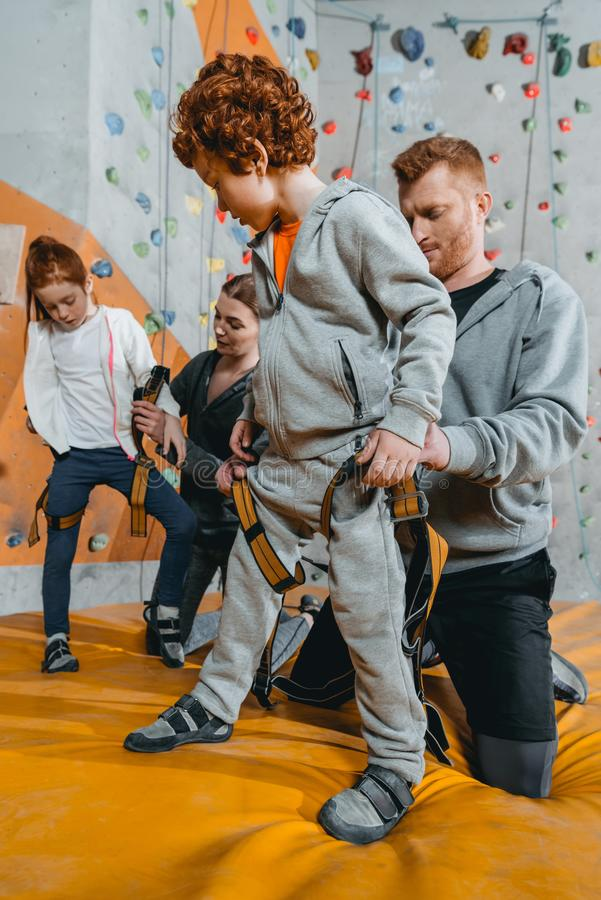 Full-length shot of young dad securing little son in a harness for climbing a wall. At gym royalty free stock photo