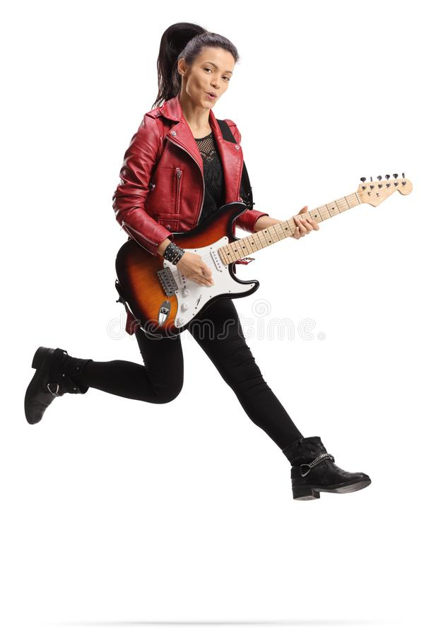 Young female guitarist playing a bass guitar and jumping. Full length shot of a young female guitarist playing a bass guitar and jumping isolated on white stock photography