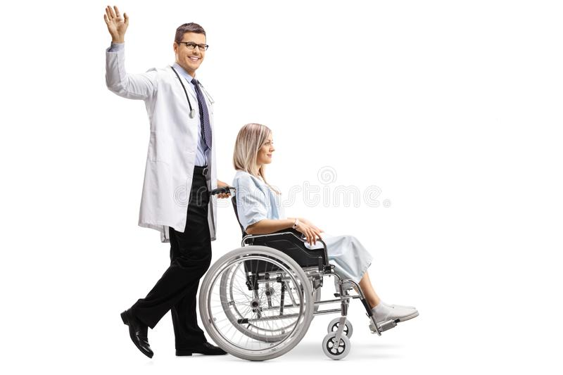 Young male doctor waving and pushing a female patient in a wheelchair royalty free stock image