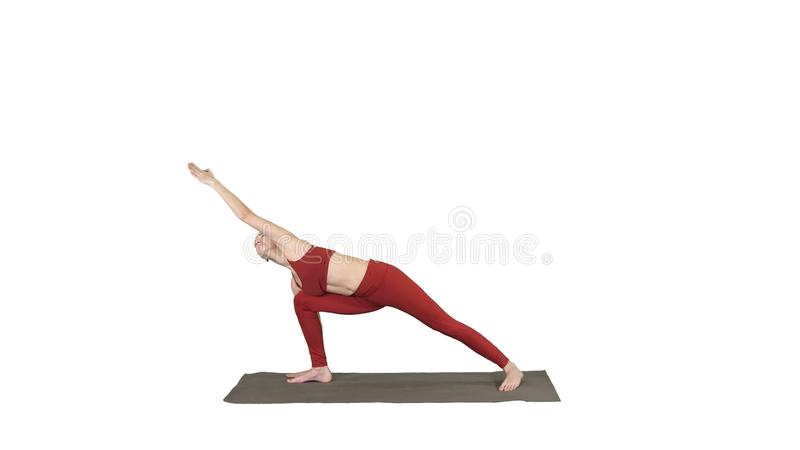 Young yogi attractive woman practicing yoga concept, standing in Utthita parsvakonasana exercise on white background. royalty free stock photo