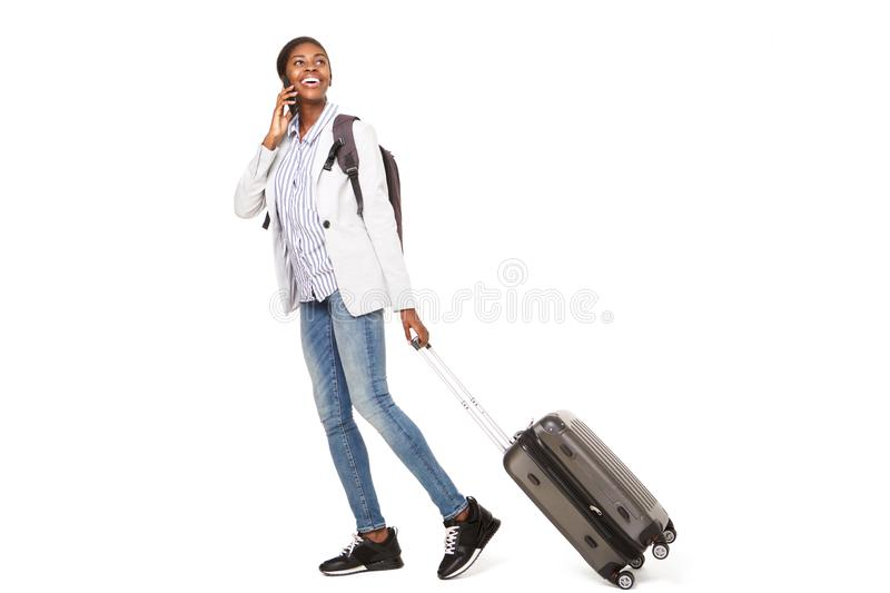 Full length side portrait of happy young black woman walking with suitcase and cellphone royalty free stock image