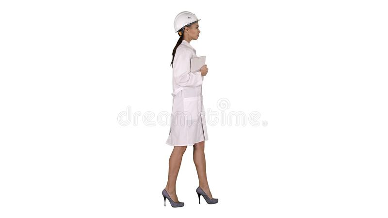 Attractive Hispanic woman in white lab coat and white safety hard hat walking holding notebook or tablet on white stock photos