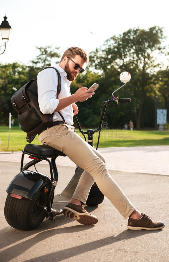 Full length side view of Bearded man in sunglasses. Sitting on modern motorbike outdoors and using smartphone royalty free stock photography
