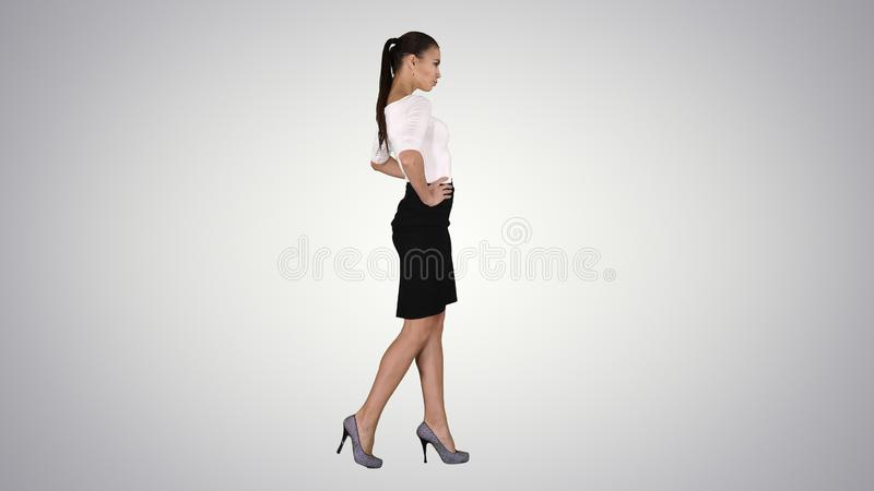 Beautiful young woman in elegant outfit walking, holding hands on hips on gradient background. royalty free stock photography