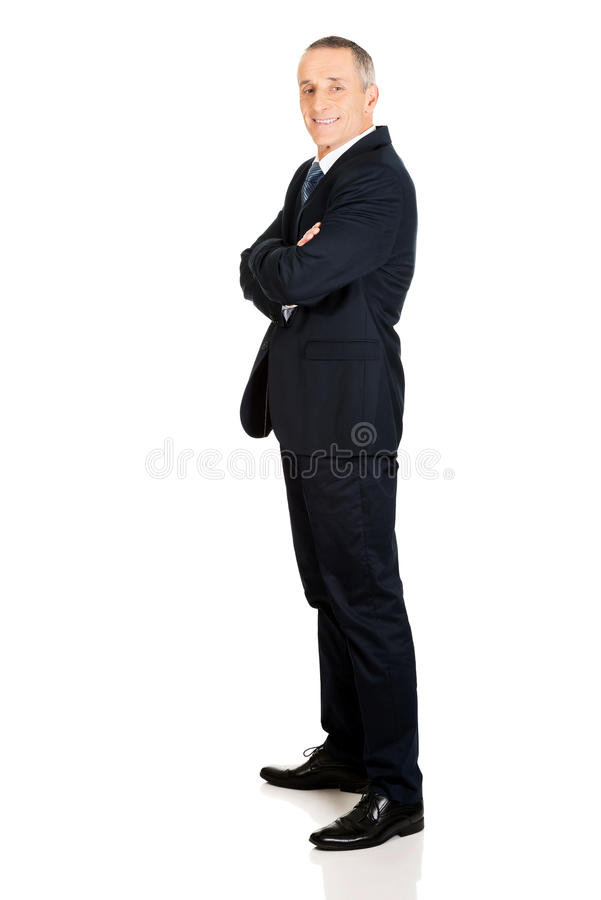 Full length side view businessman with folded arms.  royalty free stock image