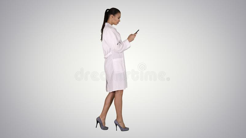 Cheerful cute young woman doctor typing text on phone while walking on gradient background. royalty free stock photos