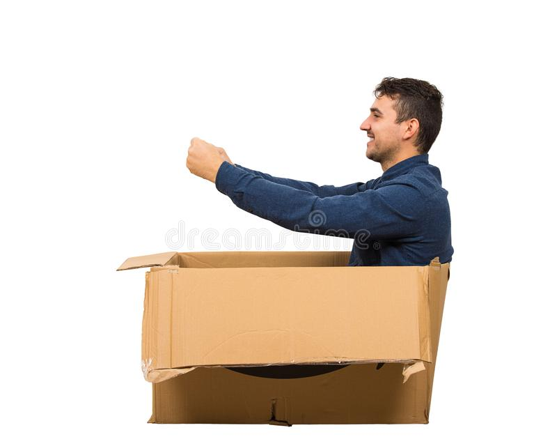 Full length side view of childish man sitting inside a cardboard box pretending to drive a new car isolated over white background royalty free stock photo