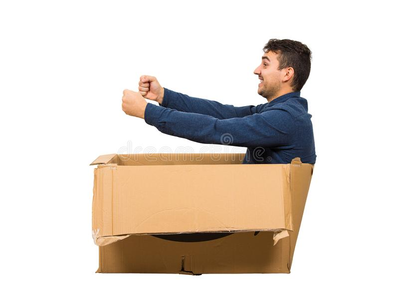 Full length side view of childish man sitting inside a cardboard box pretending to drive a new car isolated over white background stock photography