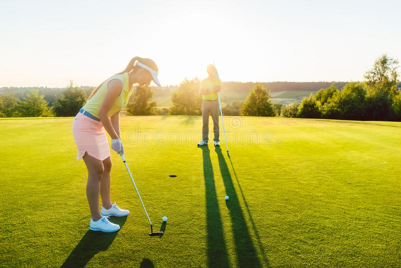 Female golf player ready to hit the ball into the cup stock images