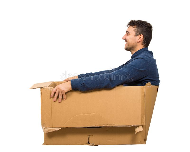 Full length side view of joyful childish man sitting inside a cardboard box isolated over white background royalty free stock photo