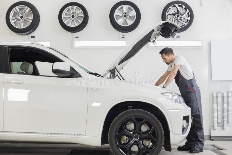 Download Full Length Side View Of Male Mechanic Examining Car Engine In Repair Shop Stock Photo - Image: 41407296
