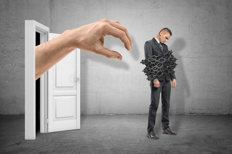 Full length side view of sad little businessman standing with chains around his body and huge hand emerging from door. Behind him. Control employees. Breach job stock image